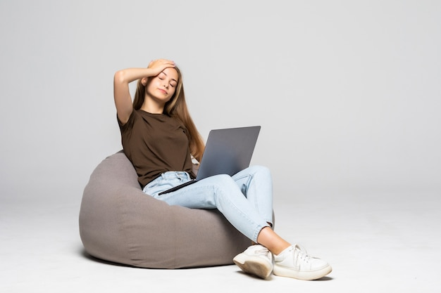 흰색 벽에 고립 된 작업에 필사적으로 컴퓨터 노트북을 사용하는 우울 하 고 좌절 여자. 우울증
