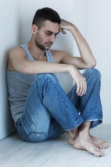 우울하고 희망이 없습니다. 우울한 젊은이 바닥에 앉아서 손에 머리를 잡고