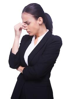 В депрессии и безнадежности. вид сбоку разочарованной молодой женщины в формальной одежде, касающейся ее носа и с закрытыми глазами, стоя изолированной на белом фоне