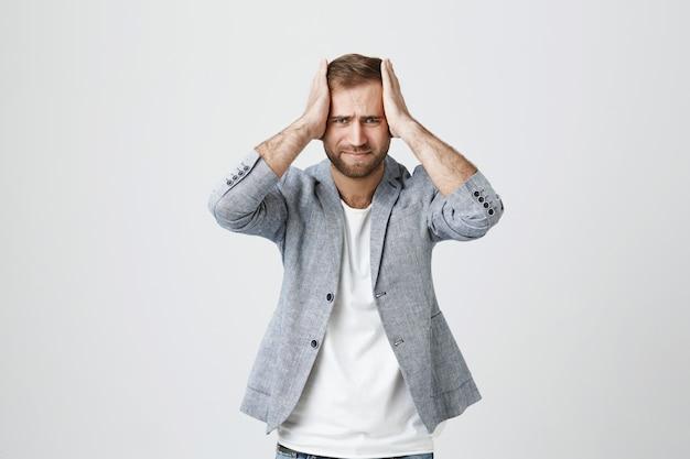 Депрессии и давления красивый парень, держась за руки на голову