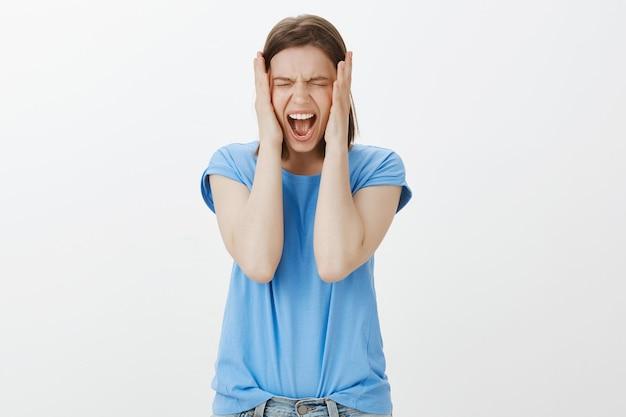 Подавленная и подавленная молодая женщина кричит, чувствует себя сытой и ненавистной, кричит
