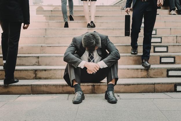 Подавленный и уставший бизнесмен сидит на лестнице в городе