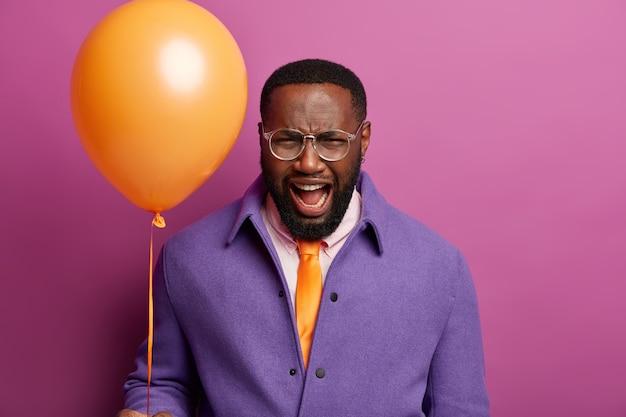 Подавленный злой мужчина кричит от негативных эмоций, испортил вечеринку, кричит на шумных гостей, держит надутый воздушный шар, носит яркую одежду