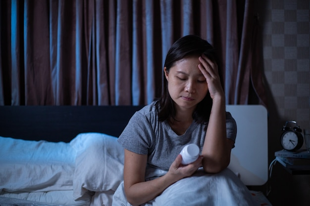 우울한 아시아 여성은 침대에서 잠을 잘 수 없습니다. 걱정스러운 소녀는 침실에서 사용하기 전에 세부 사항을 확인하기 위해 앉아서 약을 들고 있습니다. 두통과 건강이 좋지 않은 후 질병 통증.