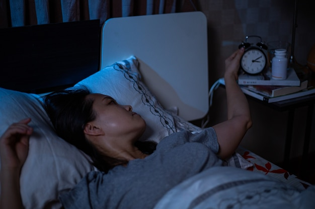 Depressed asian woman can not sleep on the bed.insomnia syndrome sleepless after unhappy and worry her lifestyle.adult feel sadness.bad emotion.