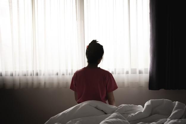 우울한 아시아 여성은 아침에 침대에 앉아 슬프고 외로운 느낌을 받습니다.