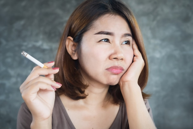 Depressed asian woman smoking cigarette with unhappy face