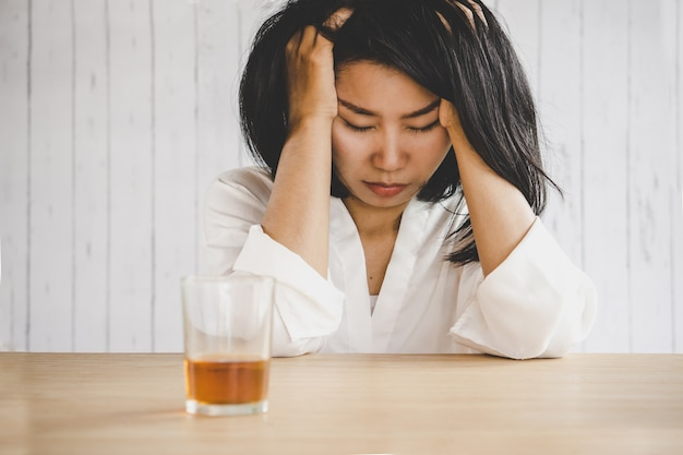 Depressed asian woman with drinking glass of alcohol