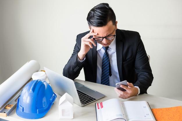 落ち込んでいるアジアの青年実業家は、電話で企業アプリをチェックし、オフィスの作業テーブルに座っているときにストレスを感じます。エンジニアリングおよび不動産プロジェクト。