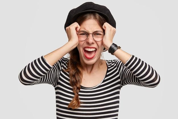 Bella giovane donna depressa vestita in stile francese, tiene le mani sulla testa, guarda disperatamente la telecamera, si sente preoccupata e stressata