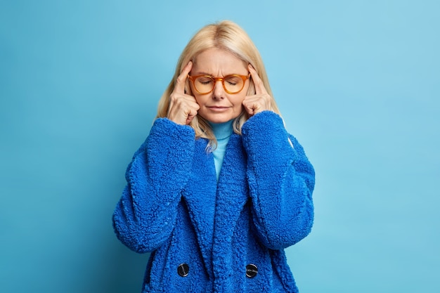Depressed blonde forty years old woman keeps fingers on temples thinks deeply or has headache closes eyes as tries to concentrate wears winter coat.