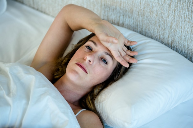 Depressed brunette wwoman lying in bed with her hand across her forehead