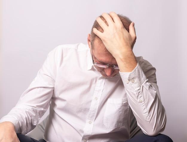 頭に手を置いて不安で落ち込んでいる実業家。パニックに疲れた男。心配している人間。