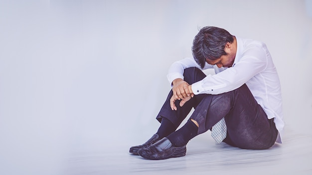 Depressed businessman sitting on the floor