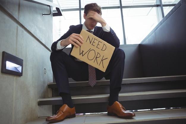 Подавленный бизнесмен, сидящий на лестнице, держа картонный лист с текстом, нуждается в работе