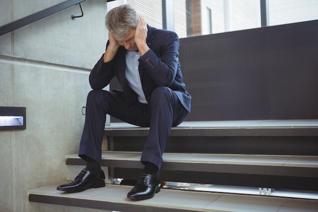 Подавленный бизнесмен, сидя на лестнице