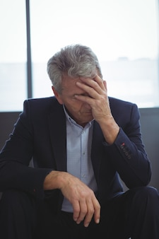 Depressed businessman sitting with hand on head