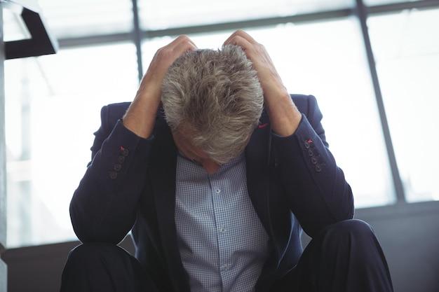 Подавленный бизнесмен сидит с рукой на голове