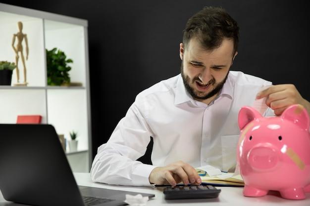 机の上の壊れた貯金箱で落ち込んでいるビジネスマンは手形を計算します