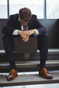 Подавленный бизнесмен с буфером обмена, сидя на лестнице