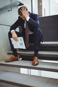 Depressed businessman with clipboard sitting on stairs