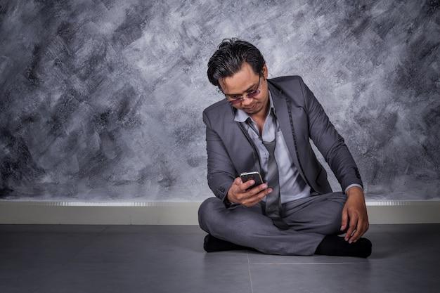 우울한 사업가 휴대 전화와 바닥에 앉아
