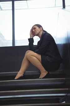 Depressed businesswoman with hand on her head sitting on stairs