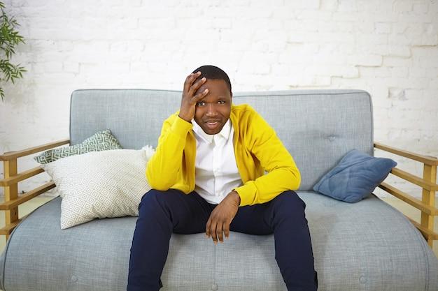 落ち込んでいるカジュアルな服装の若いアフリカ系アメリカ人男性が自宅のソファに座って、頭に手をかざし、サッカーチャンピオンシップを見て、お気に入りのチームが試合に負けている間、気分を害している