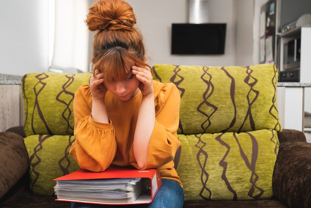 소파에 앉아 문서 더미를 보고 우울한 백인 여성