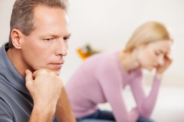 Подавленная пара. вид сбоку депрессивного зрелого мужчины, держащего руку за подбородок, пока грустная женщина сидит на фоне