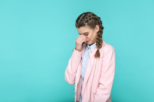 Depressed crying portrait of beautiful cute girl standing with makeup and brown pigtail hairstyle in striped light blue shirt pink jacket. indoor, studio shot isolated on blue or green background.