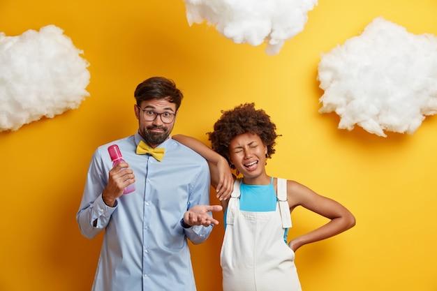 우울한 우는 젊은 아프리카 계 미국인 고위 여성은 주저로 보이는 남편의 어깨에 기댄 변덕스러운 기분을 가지고 있습니다.