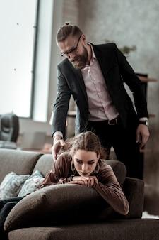 意気消沈した娘。ビジネスマンが家に帰ってきて、落ち込んで孤独を感じている娘を見ている