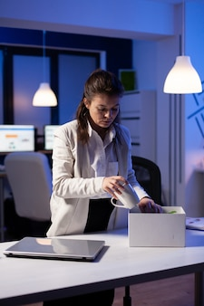 Depressed dismissed employee putting her stuff in white box from table at office as being fired