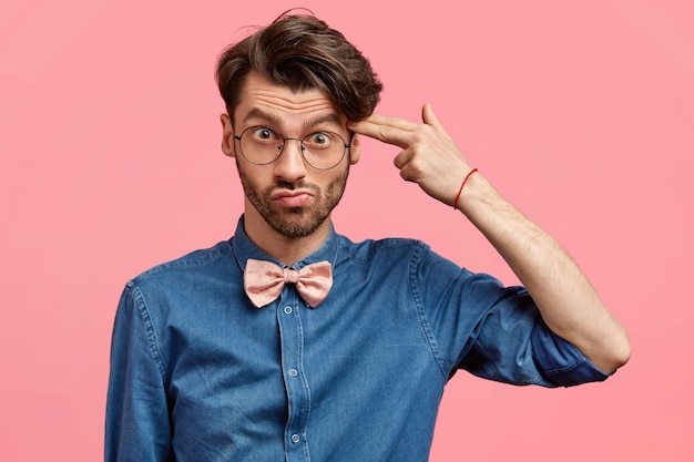Depressed displeased unshaven male with trendy haircut, pretends killing himself, shoots with fore finger in temple, dressed in denim shirt and pink bowtie, feels tired of difficult life. negativity