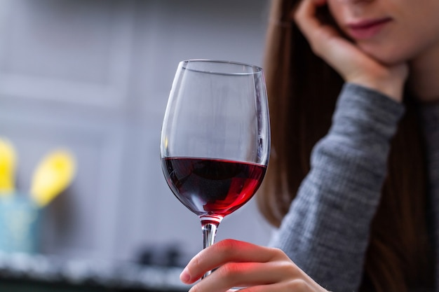Depressed, divorced crying woman sitting alone in kitchen at home and drinking a glass of red wine because of problems at work and troubles in relationships. social and life problems