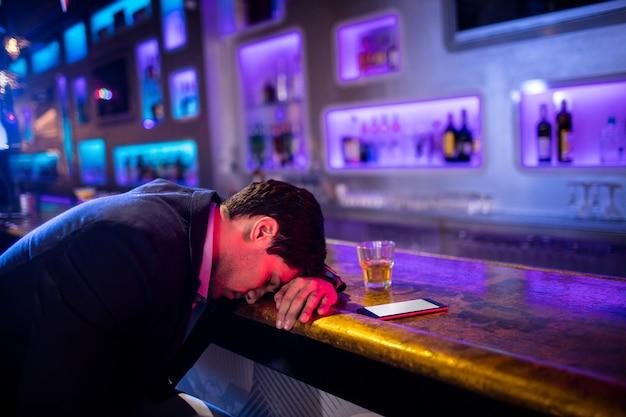 テーブルの上に頭で寝て落ち込んで酔って男