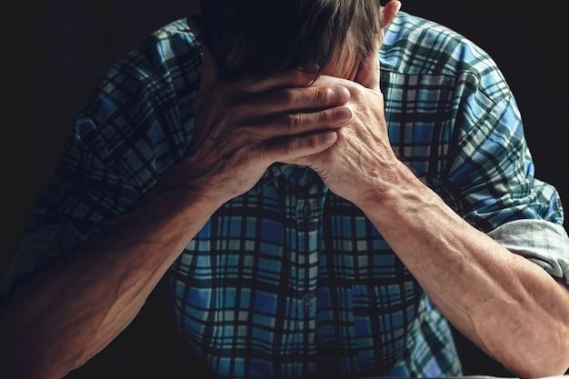 落ち込んでいる老人は彼の手で顔を覆っています