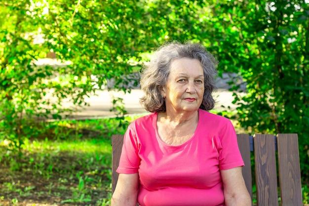 Подавленная пожилая женщина вдумчивая, сидя на скамейке в парке в солнечный летний день. зрелая женщина в яркой футболке думает о грустном. психология. серьезное и вдумчивое выражение