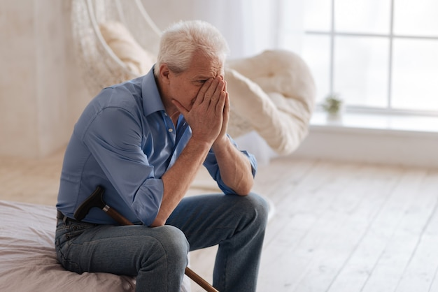 Depressed emotional aged man sitting on the bed and covering his face while crying