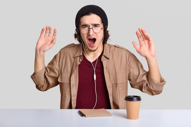 Depressed emotive guy raises hands and exclaims desperately, has annoyed facial expression, wears round optical spectacles, listens music, writes notes in notepad, isolated on white