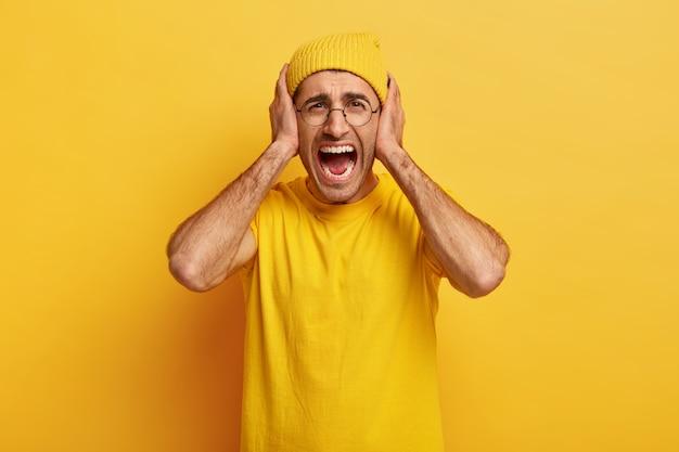 우울한 지친 스트레스가 많은 남자는 화를 풀고 큰 소리로 비명을 지르며 귀를가립니다.