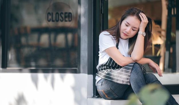 우울한 여성 기업가는 문제에 직면 한 사업에 두통을 느끼고 사업을 종료해야합니다.