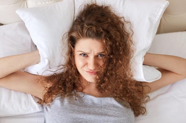 우울 좌절 여성은 침대에 누워있는 동안 베개로 귀를 덮고, 코를 stand 수 없으며, 잠을 잘 수 없습니다