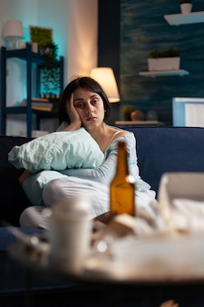 枕を持って一人で座っている落ち込んで欲求不満ストレストラウマの女性
