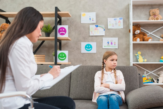 우울한 소녀 클립 보드에 여성 심리학자 쓰기 메모와 함께 소파에 앉아