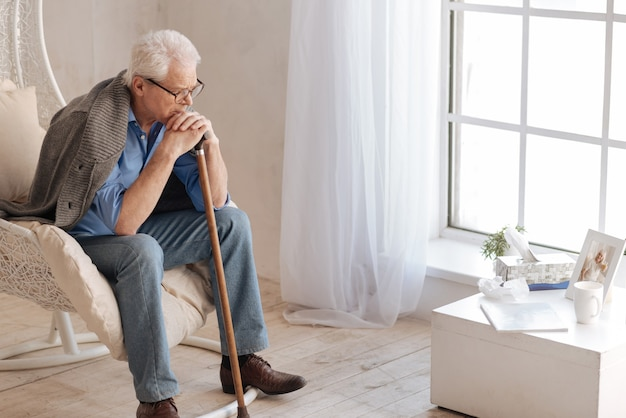 Подавленный мрачный пожилой мужчина сидит в кресле и смотрит на фото своей жены, опираясь на трость