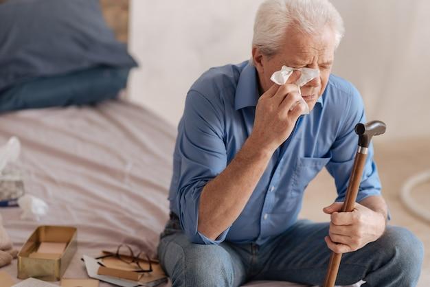 Подавленный мрачный пожилой мужчина плачет и вытирает слезы, держа бумажную салфетку