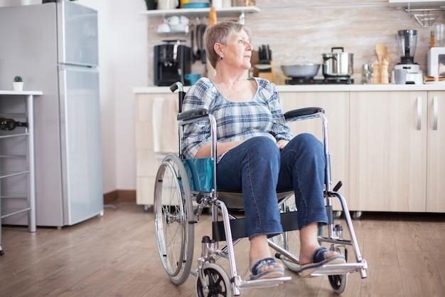 足の怪我から車椅子で落ち込んでいる障害のある年配の女性。悲しみ、心配、悲しみに満ちた病人のためのリハビリ、麻痺、障害のある高齢者の年金受給者。 olの退職期間