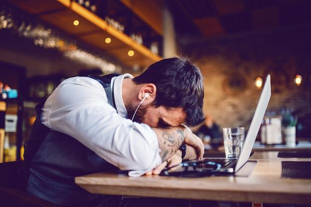 Подавленный красивый кавказский бизнесмен только что неловко разговаривал за ноутбуком. интерьер кафе.